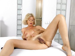 Mature babe with a bush masturbates solo in bed