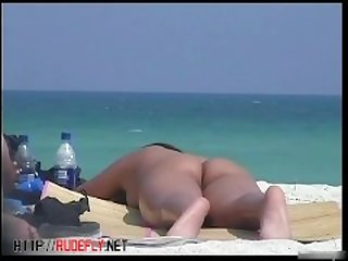A nude tanned skinny lady with perfect breasts on a beach texting