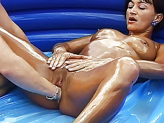 Oiled stepmom gets fisted outdoors